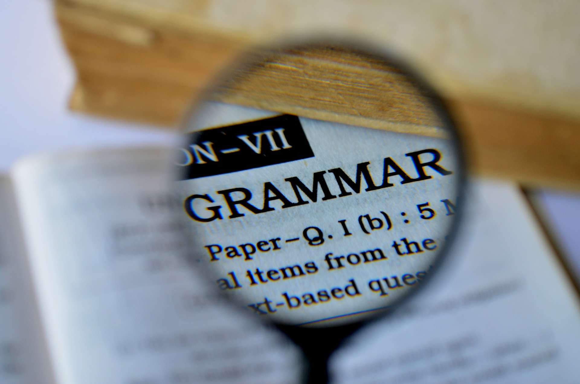 """Magnifying glass held over text displaying the word """"Grammar"""""""