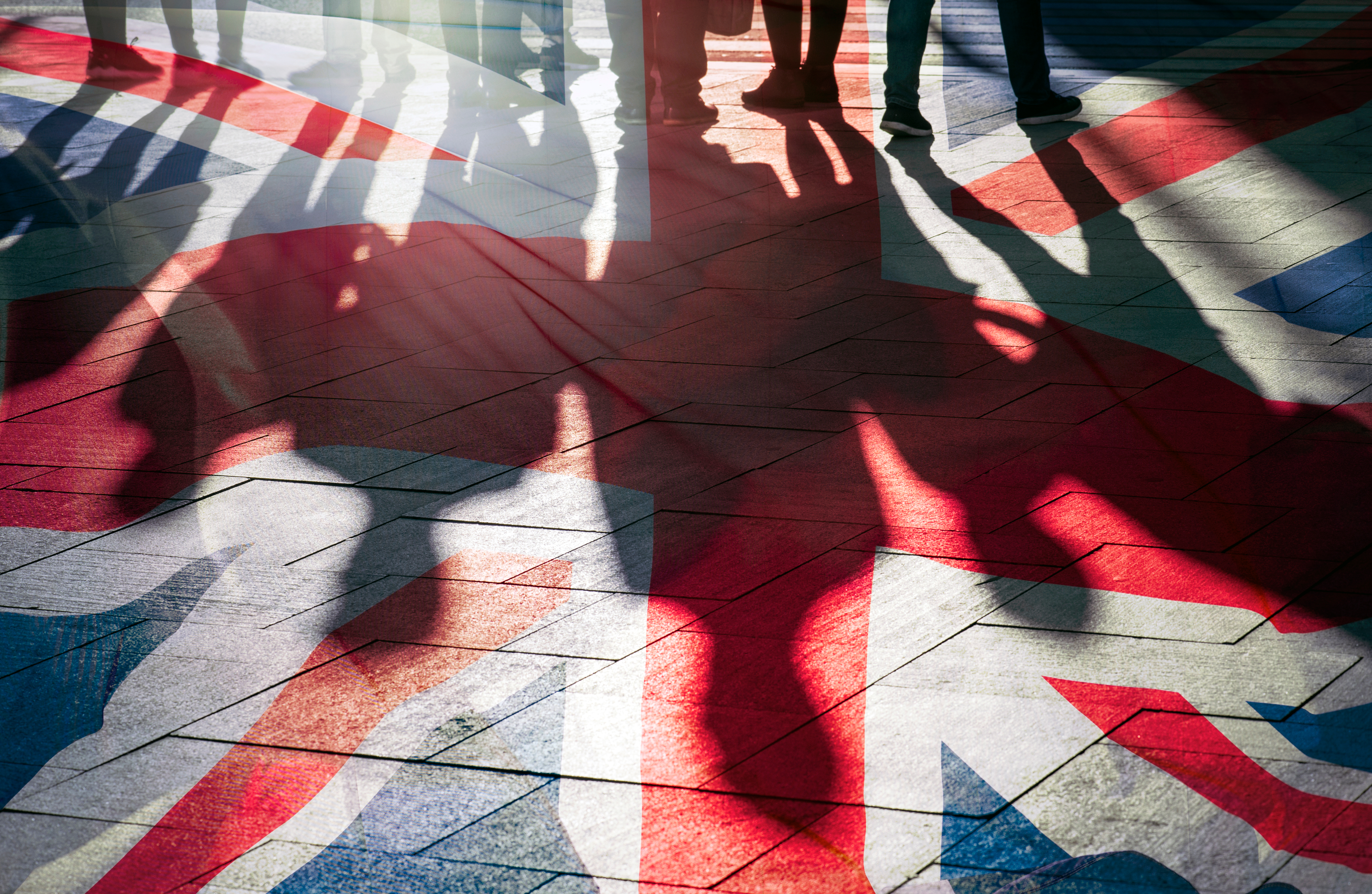 Shadows of people in front of UK flag