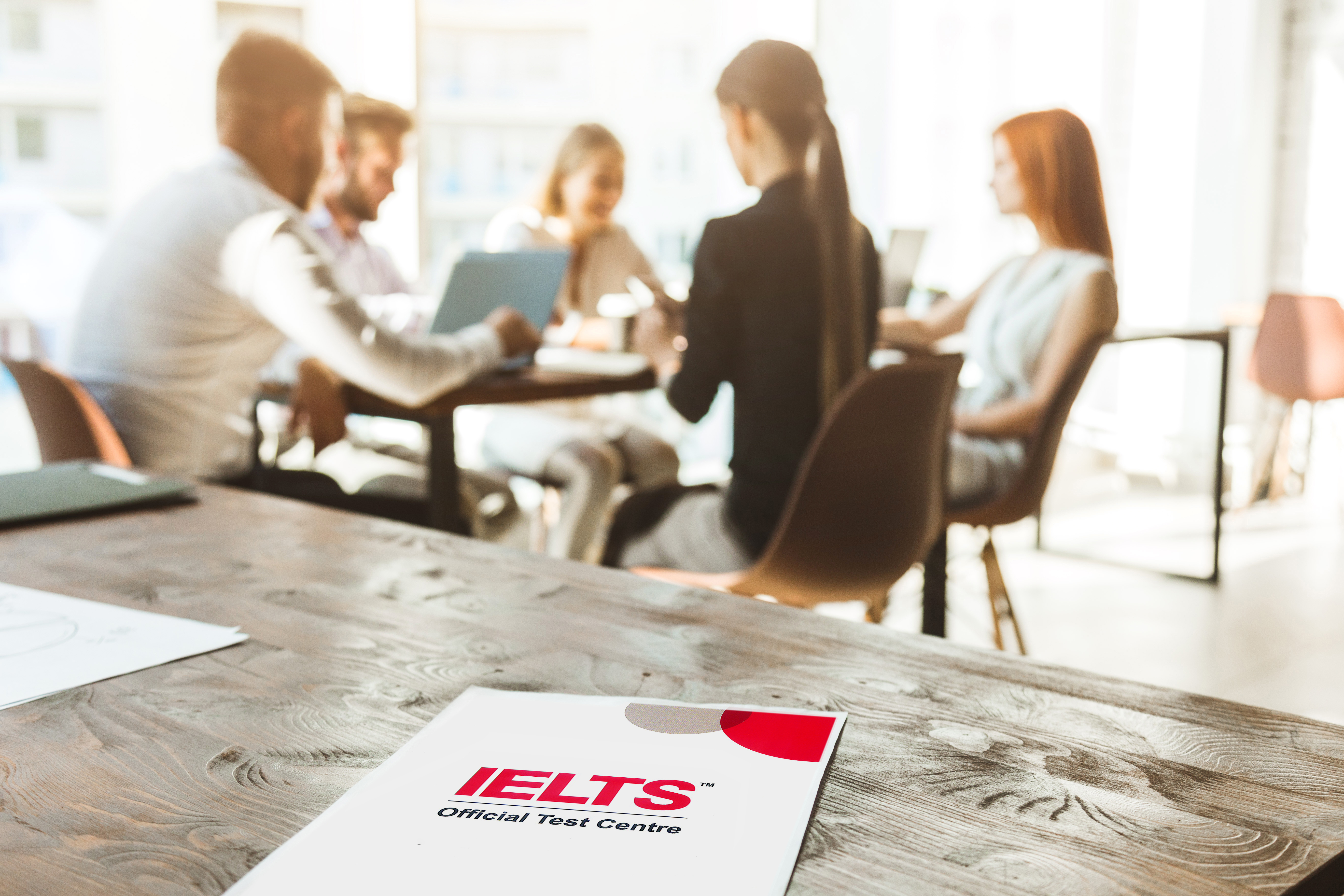 Group of learners around a table with an IELTS document