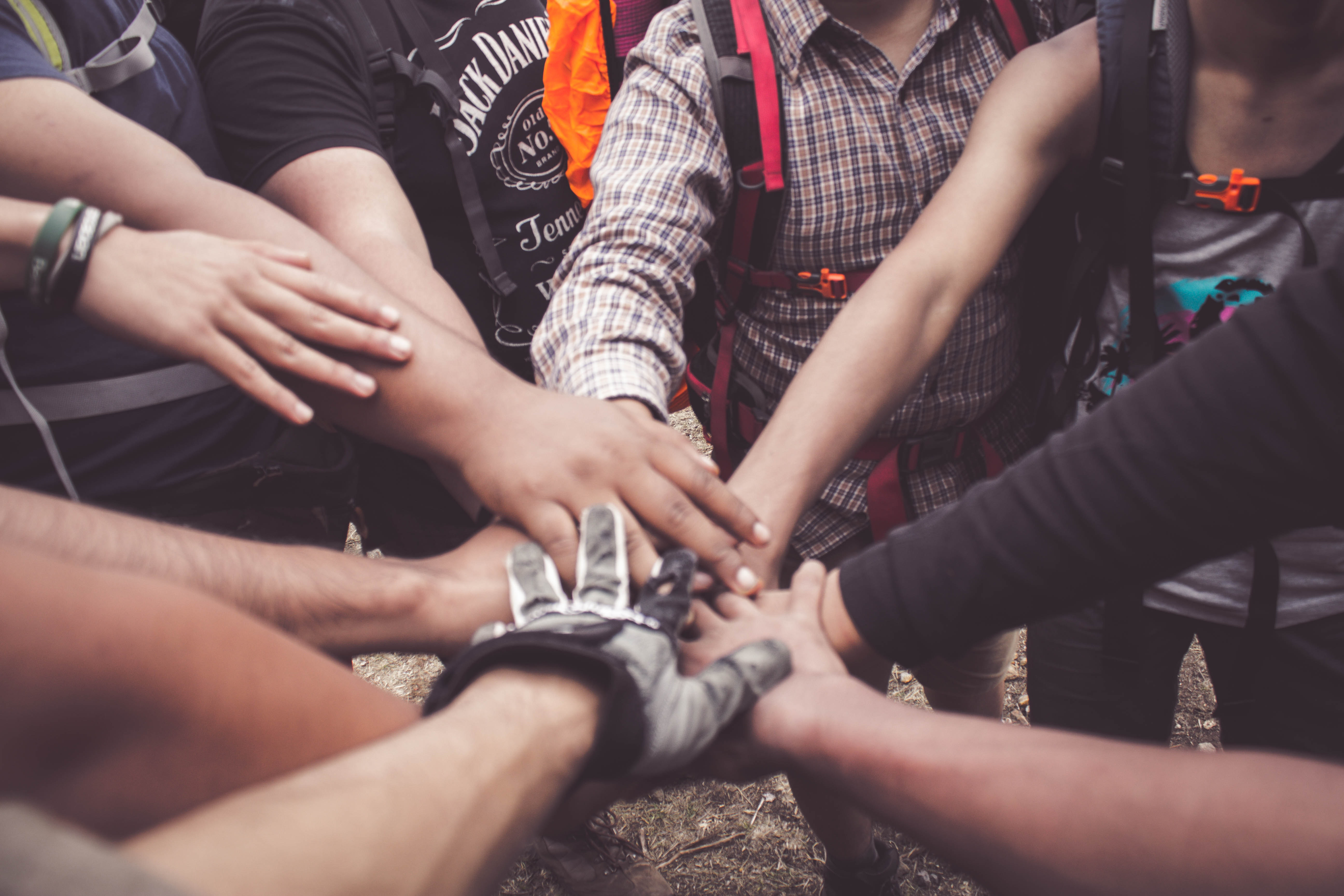 Diverse group of people standing in a circle with their hands touching in the middle