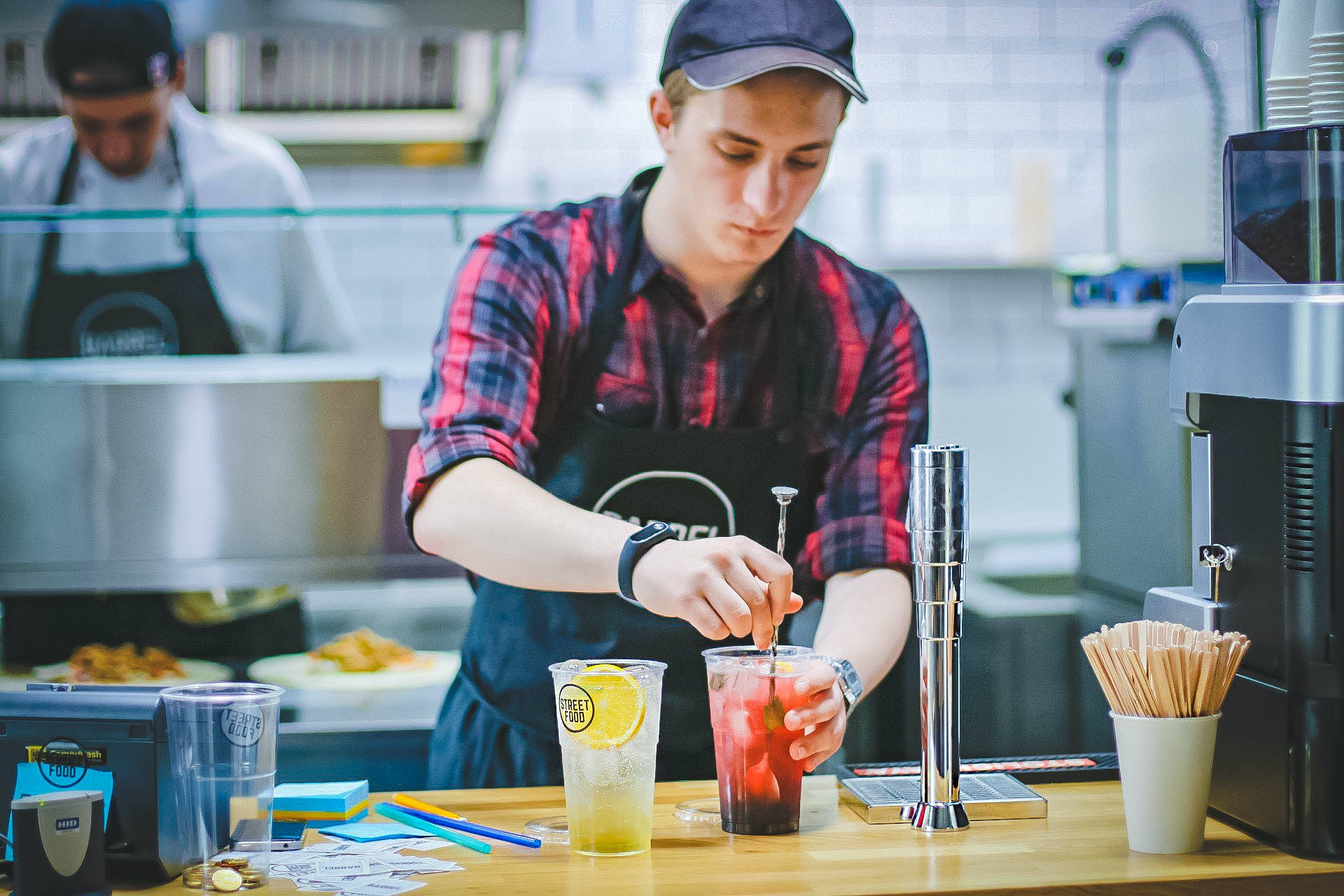 Person working in a kitchen making a drink for a customer